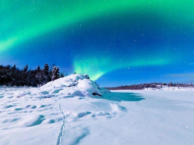 Заснеженное поле в северном сиянии