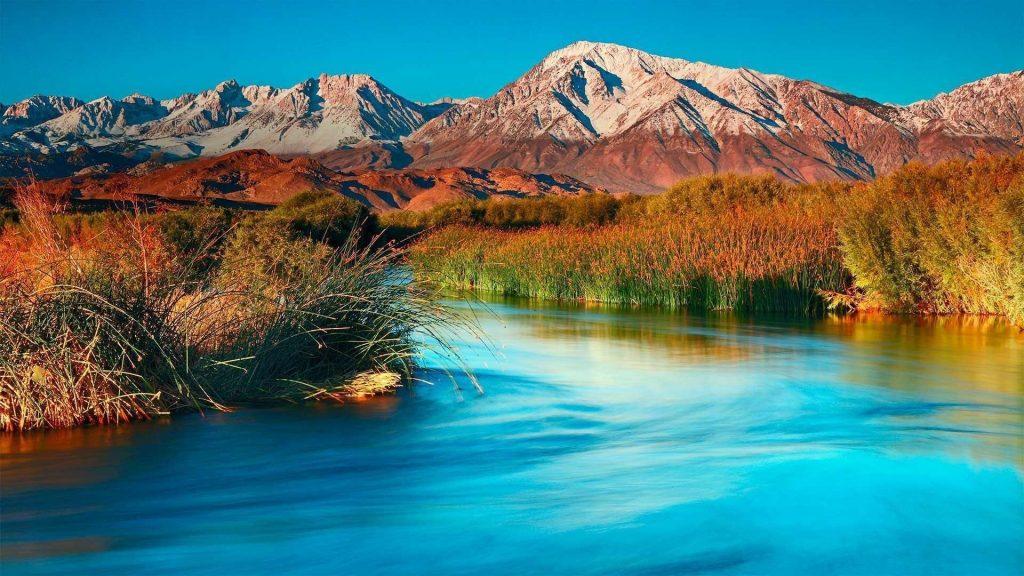 Река между зелеными и сухими травами и растениями покрытое поле и пейзаж вид на коричневые горы природа обои скачать