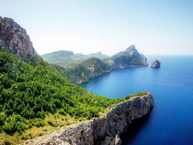 Белая скалистая гора рядом с голубым морем под голубым небом покрытая зелеными деревьями в дневное время природа