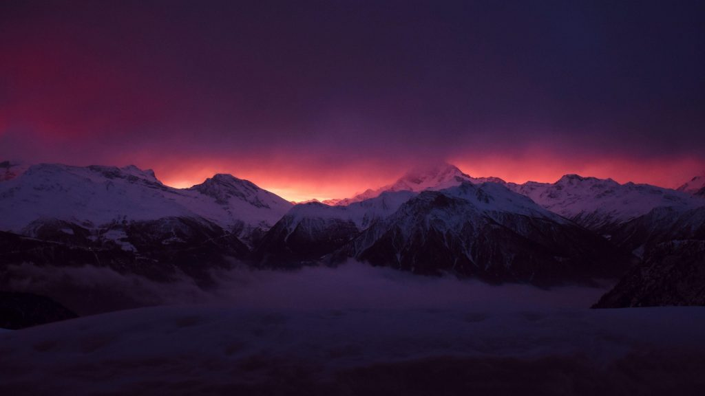 Заснеженные вершины гор туман под фиолетово черным облачным небом природа обои скачать