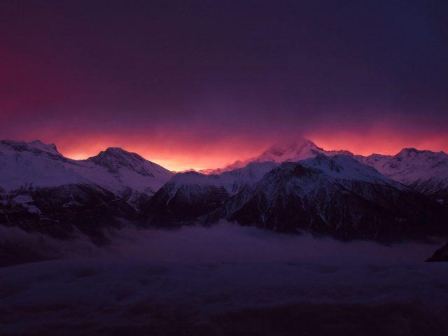 Заснеженные вершины гор туман под фиолетово черным облачным небом природа