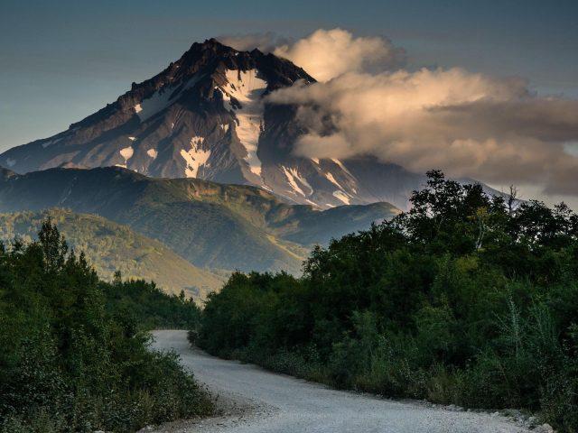 Облака покрыли гору под серым бетоном дорога между зелеными деревьями природа