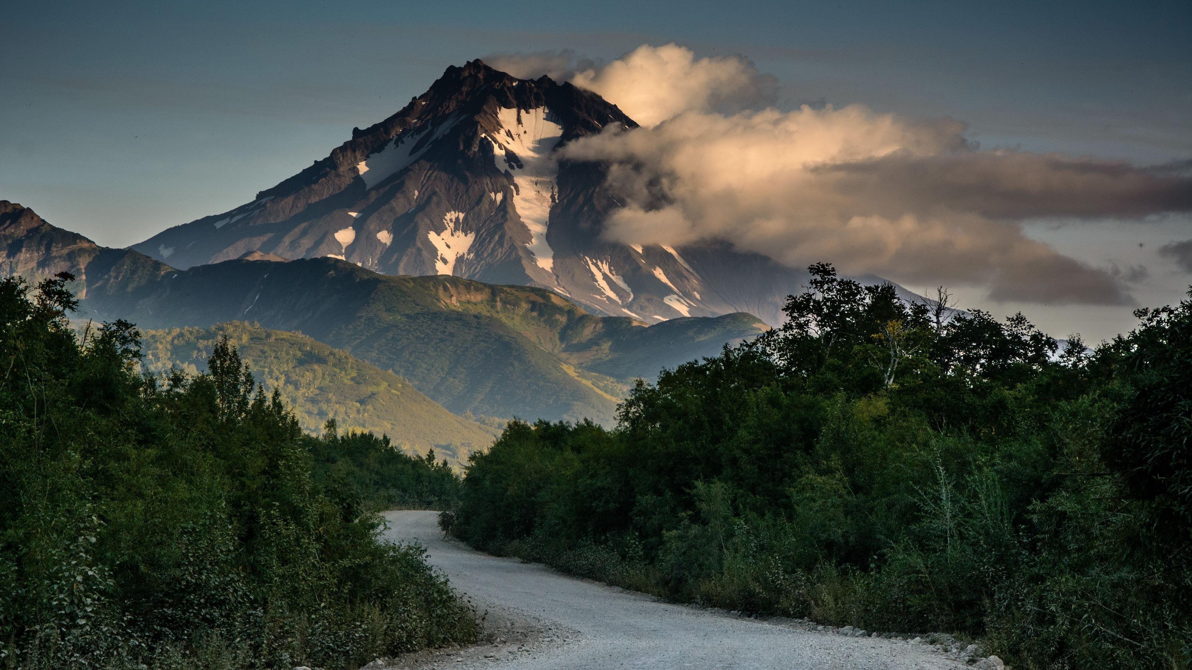 Облака покрыли гору под серым бетоном дорога между зелеными деревьями природа обои скачать