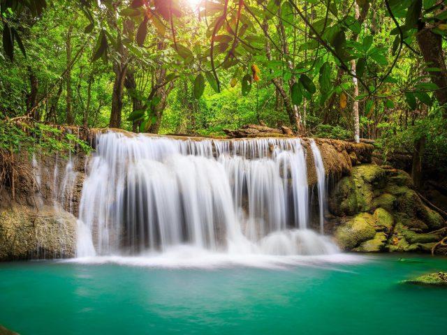 Водопады на скале льются на реку в окружении зеленых деревьев лес солнечный луч фон природа