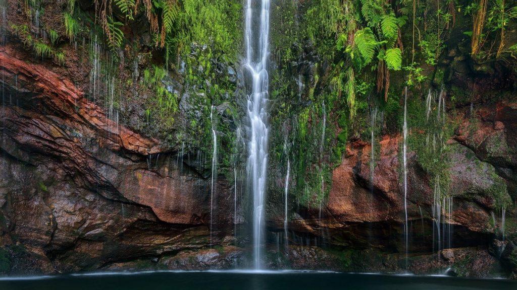Водопады на покрытых зелеными растениями скалах льются на речную природу обои скачать