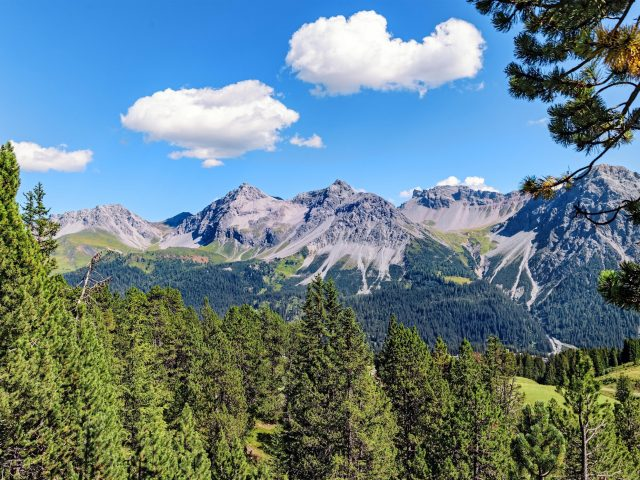 Горы под голубым небом и белыми облаками днем с зелеными деревьями природа