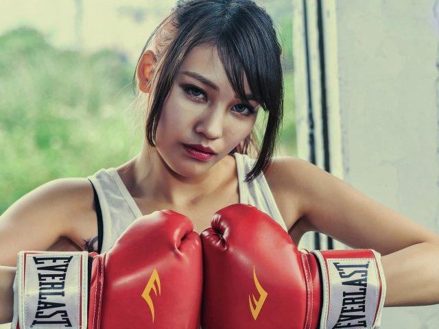 Голубые глаза бокс брюнетка девушка с красными перчатками на синем фоне бокс