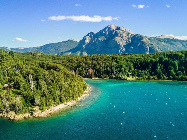 Вид с высоты птичьего полета на реку между зелеными деревьями покрытый лесом и пейзажем вид на горы под голубым небом природа