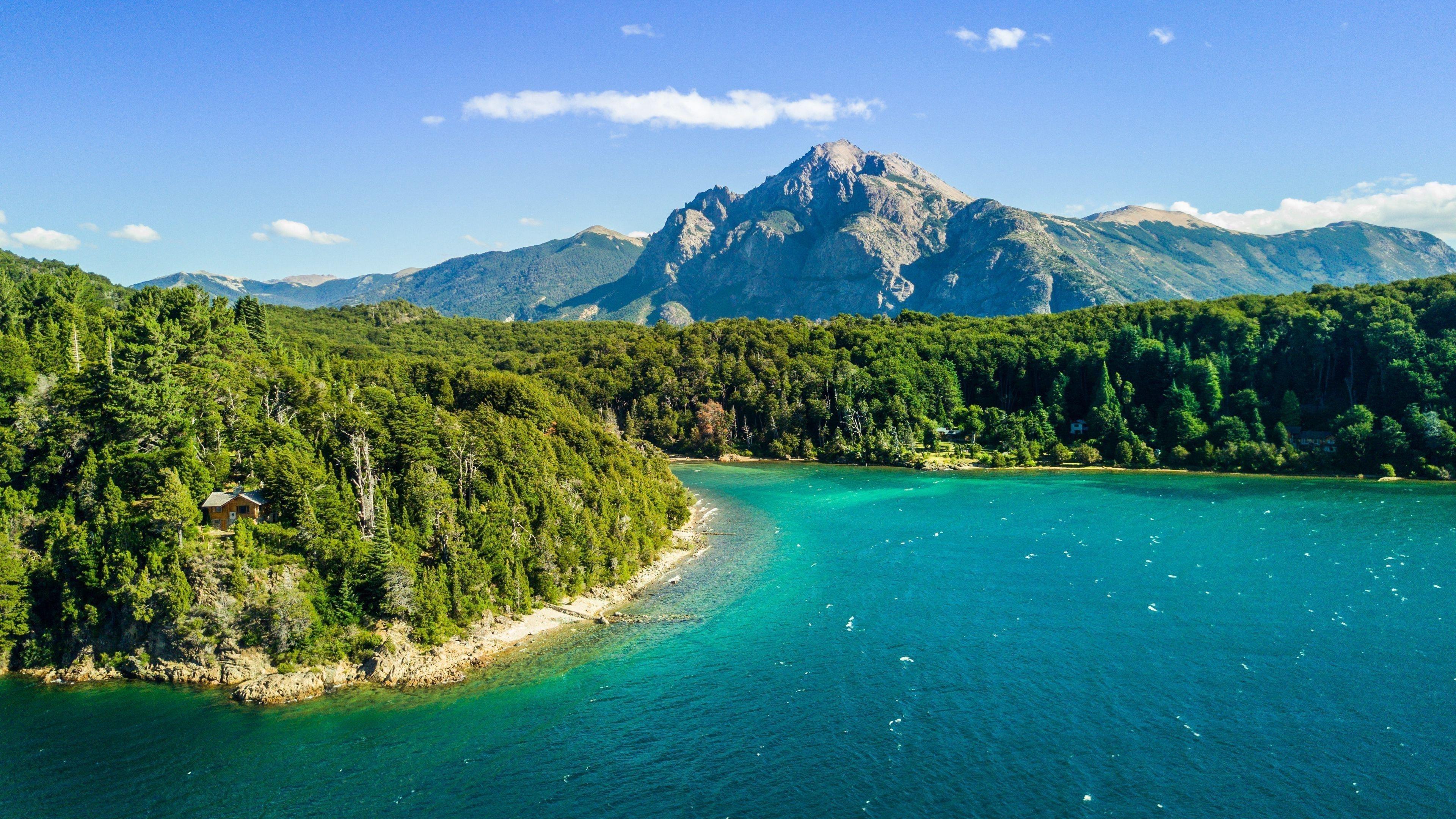 Вид с высоты птичьего полета на реку между зелеными деревьями покрытый лесом и пейзажем вид на горы под голубым небом природа обои скачать