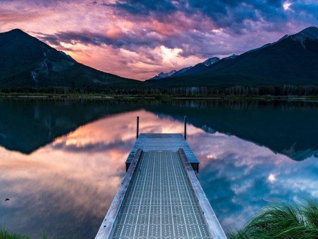 Пирс горы берег озера отражение на фоне гор под черно-розовой облачной природой