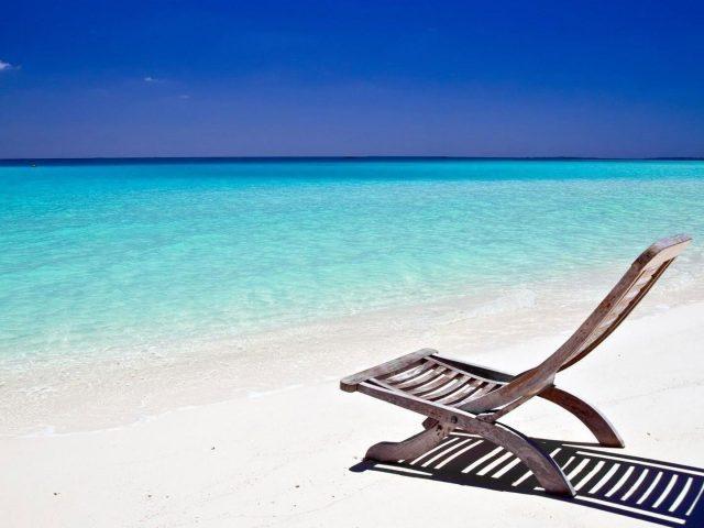 Деревянный пляжный стул на песке в солнечное время пляж