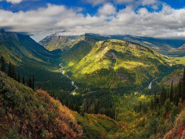 Покрытая зеленью гора под белыми облаками с зелеными деревьями в дневное время природа