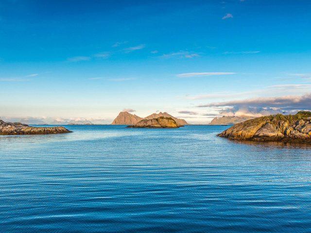 Зеленые покрытые скалы в водоеме под голубым небом в дневное время природа