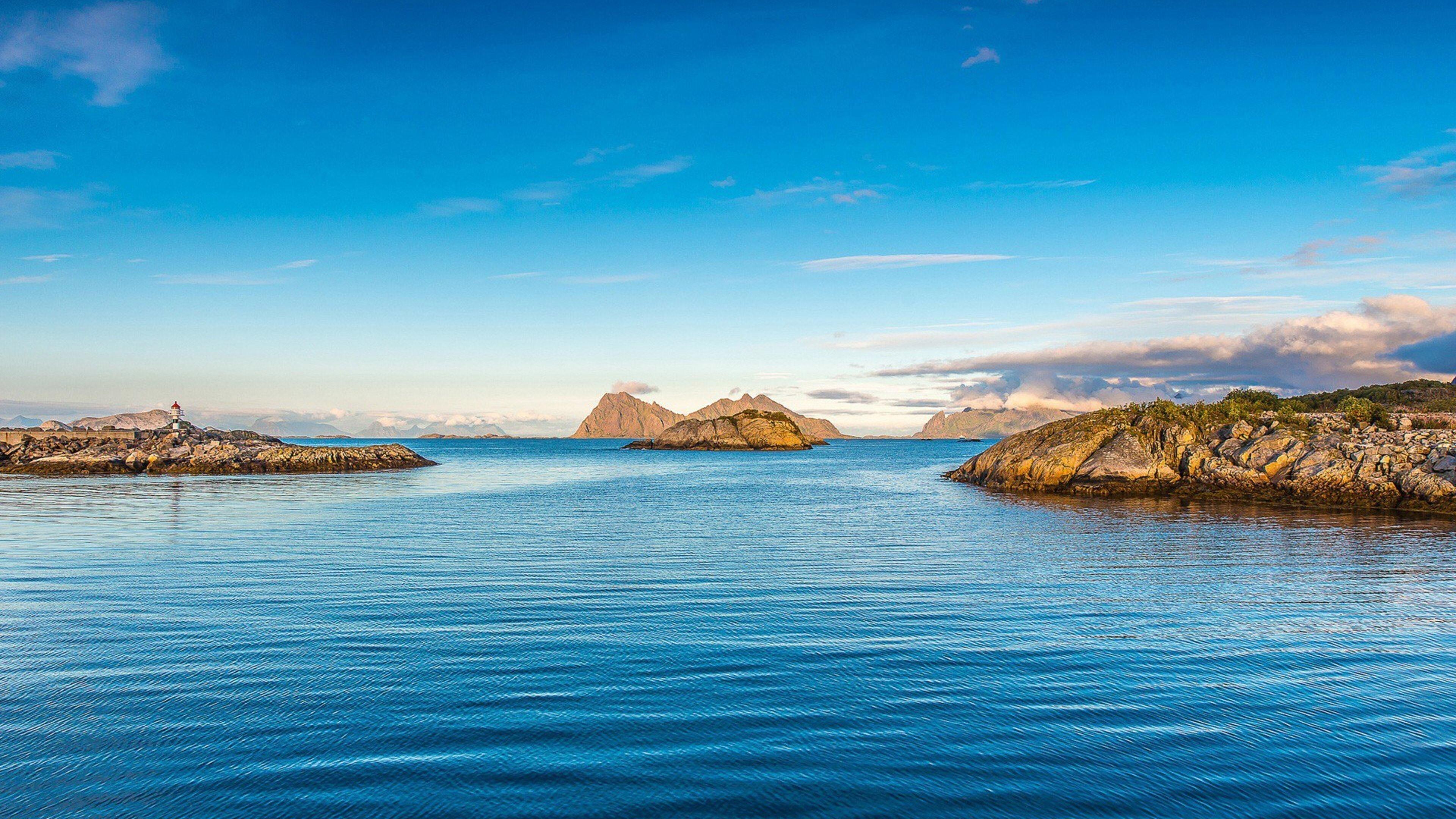 Зеленые покрытые скалы в водоеме под голубым небом в дневное время природа обои скачать