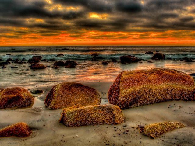 Коричневые скалы перед берегом моря с черными и красными облаками природа