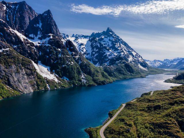 Дорога между белыми черными покрытыми горами с рекой и зелеными деревьями покрытыми горами в дневное время природа