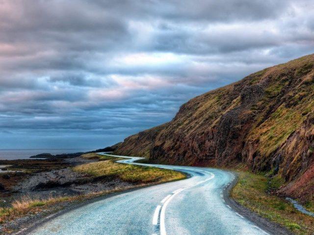 Дорога между зелеными водорослями, покрытыми скалами, вода под черно-белыми облаками, небо, природа