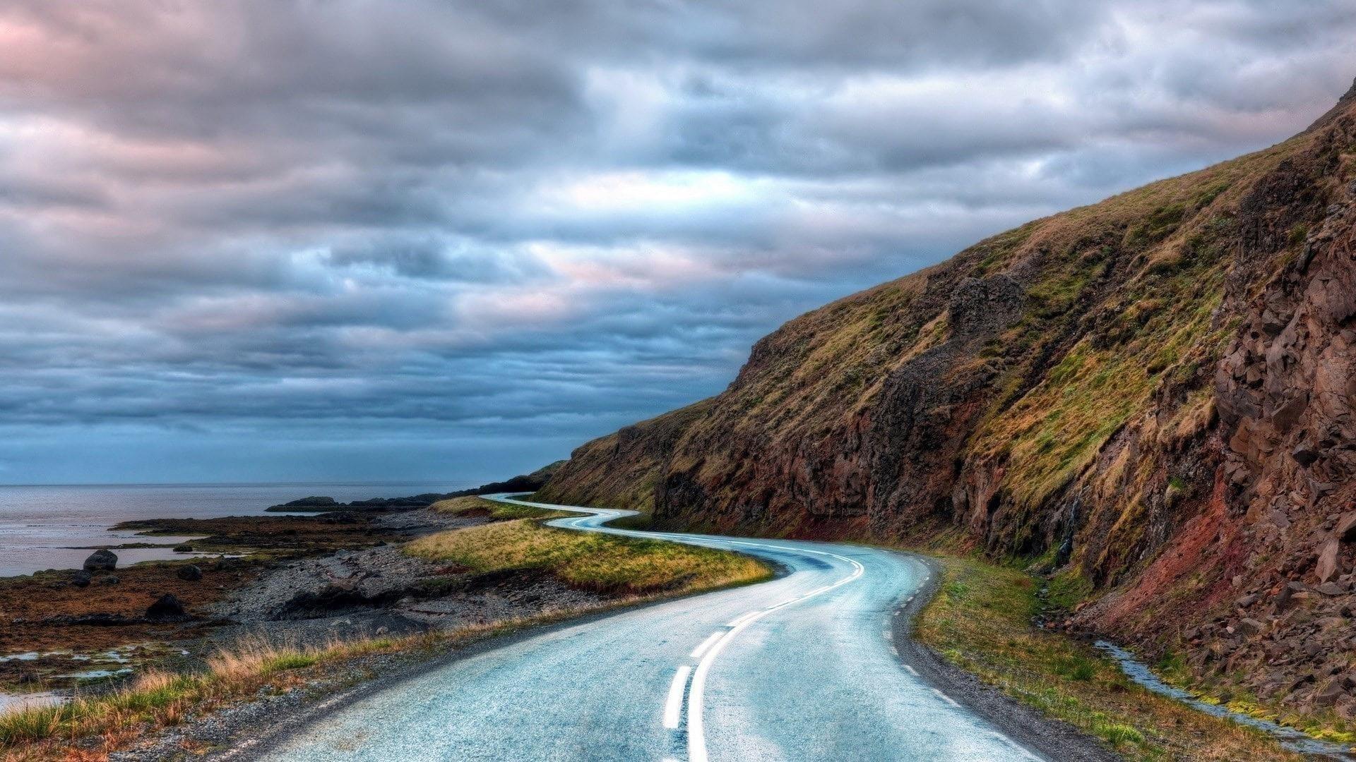 Дорога между зелеными водорослями, покрытыми скалами, вода под черно-белыми облаками, небо, природа обои скачать