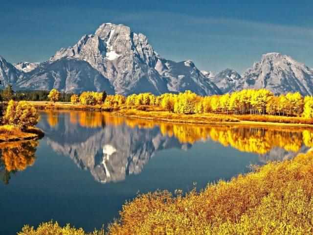 Река с пепельным цветом горное отражение окруженное желтыми листьями деревьев в дневное время природа