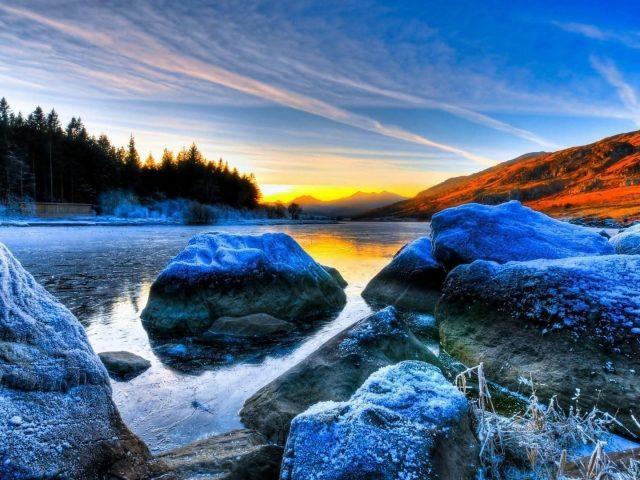 Замерзшие скалы на реке пейзаж вид деревьев на фоне восхода солнца под голубым небом природа