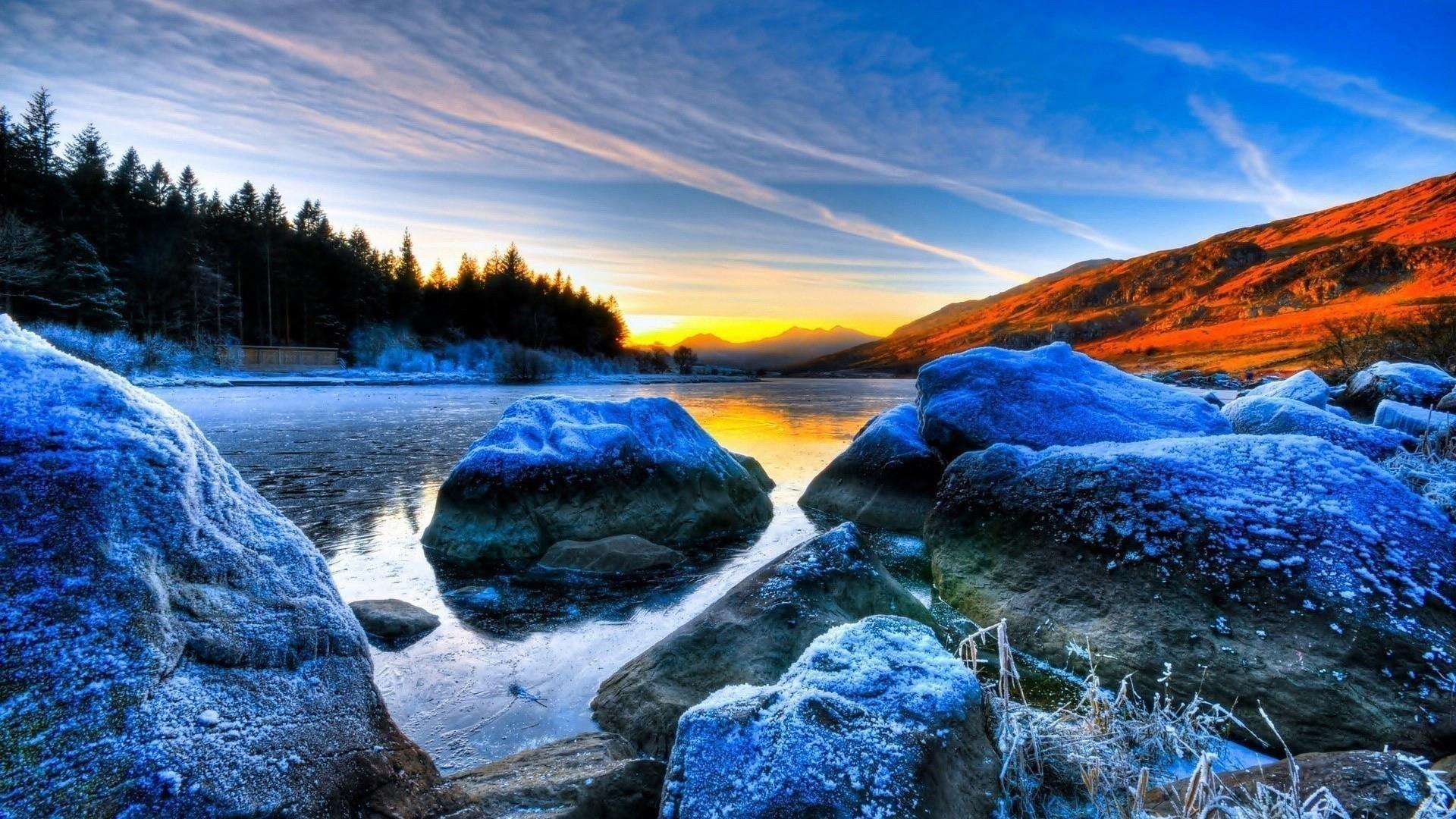Замерзшие скалы на реке пейзаж вид деревьев на фоне восхода солнца под голубым небом природа обои скачать