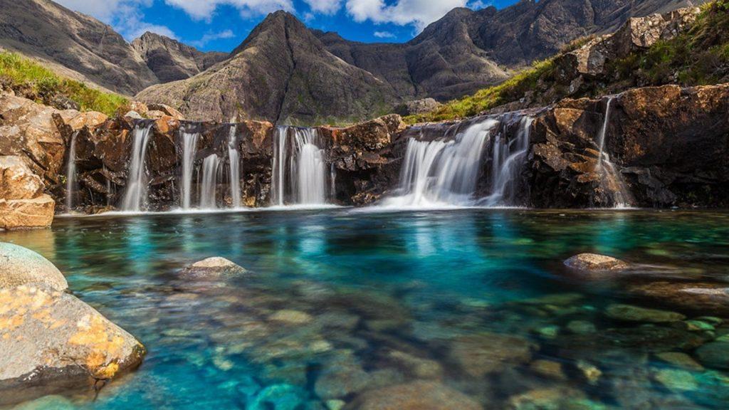 Многочисленные водопады льются на реку с пейзажем гор под голубым облачным небом природа обои скачать