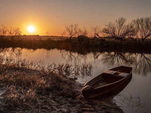 Посадка лодки между озерами под закатом солнца