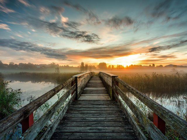 Деревянный мост и озеро под голубым небом с облаками во время заката природа