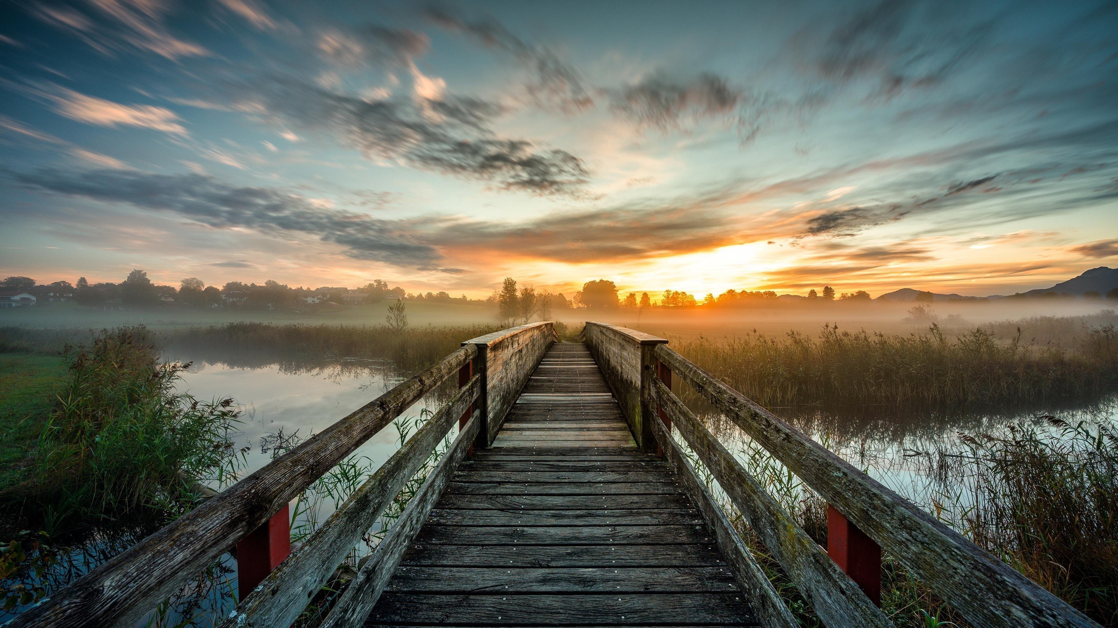 Деревянный мост и озеро под голубым небом с облаками во время заката природа обои скачать