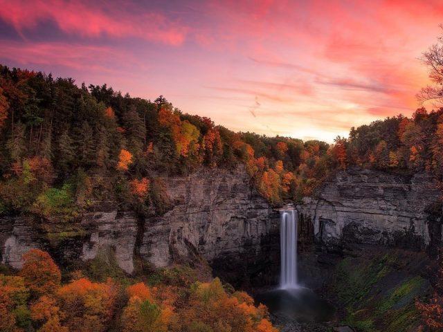 Водопад между осенними деревьями покрытый лесом с красочной закатной природой