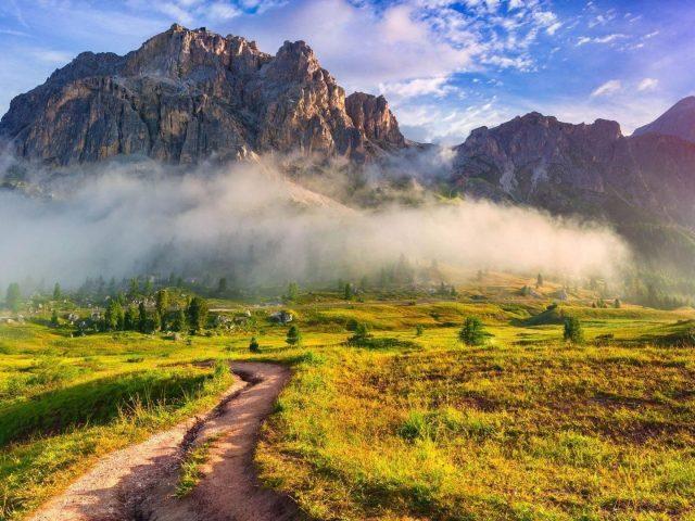 Песчаная дорожка между зеленой травой, полем, землей, покрытым туманом, склоном, горами, голубым небом, фоном природы