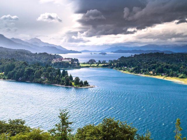 Пейзаж Аргентины лес озеро и зеленые деревья покрытые горами под облачным небом природа