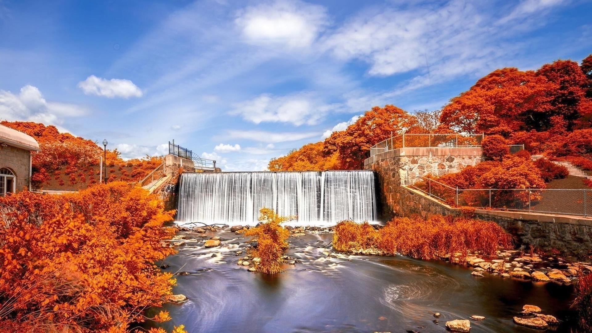 Водопад плотина водопад между осенними деревьями под пасмурным голубым небом природа обои скачать