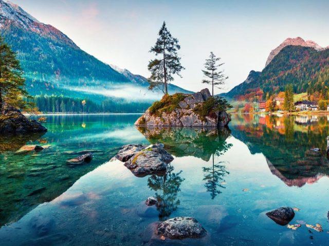 Покрытая зеленью гора под озером отражение между зелеными деревьями природа