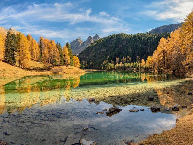 Зелено желтые осенние деревья с отражением на озере лай да пальпуонья в Швейцарии природа