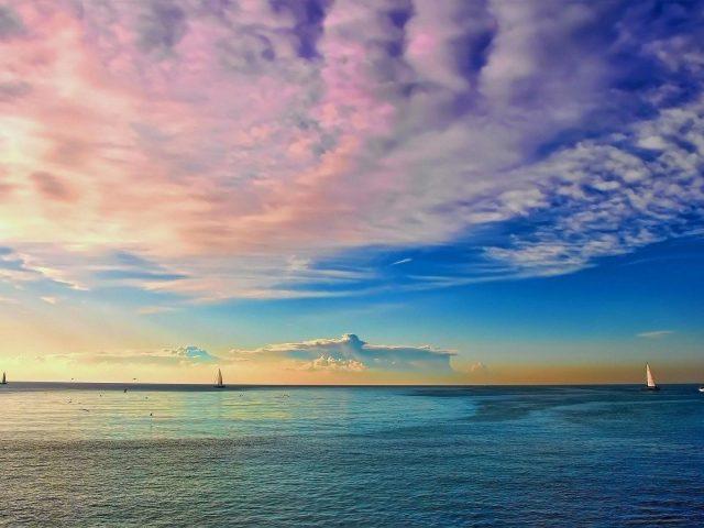 Розово бело голубое облачное небо над спокойным океаном природа