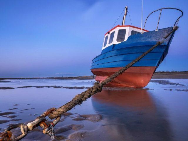 Голубое небо и рыбацкая лодка пойманная в ловушку якорем пойманная на веревке природа