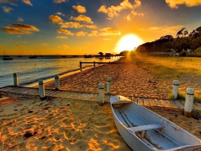 Белая лодка на берегу моря во время заката природа