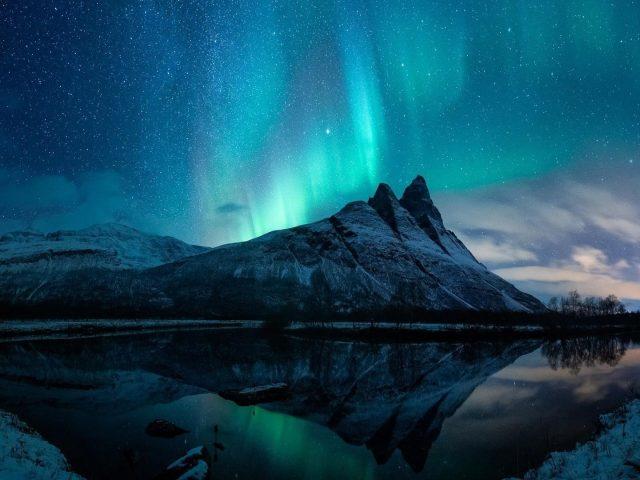 Снежное северное сияние горы в ночное время с отражением на водоеме природы