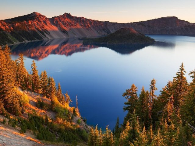 Покрытая деревьями скала посреди спокойного озера окруженная покрытыми песком горами и зелеными деревьями с отражением природы