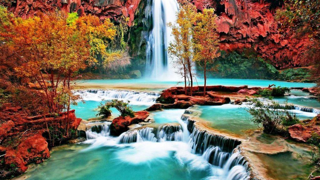 Водопад между покрытыми водорослями скалами льется по ручью реки в окружении разноцветных деревьев природы обои скачать
