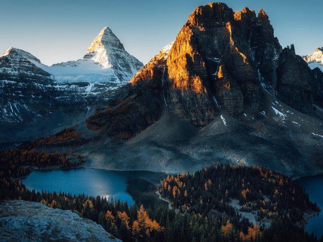 Заснеженная гора и вид с высоты птичьего полета на озеро окруженное деревьями природа