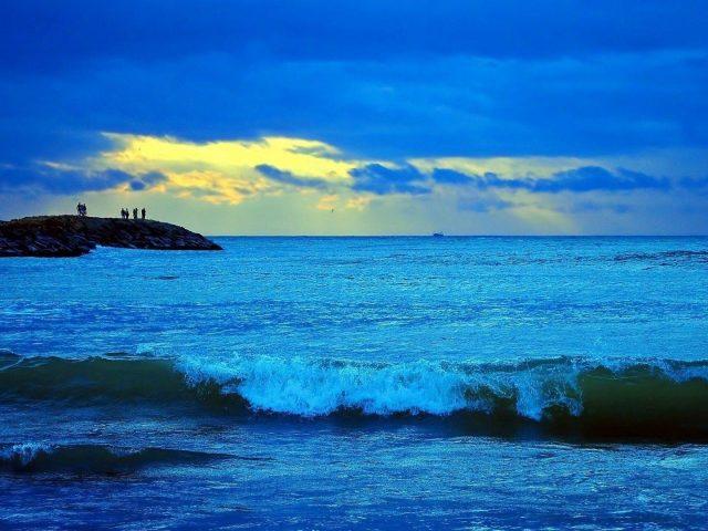 Морской прибой под голубым облачным небом и пейзажный вид скал с людьми природа