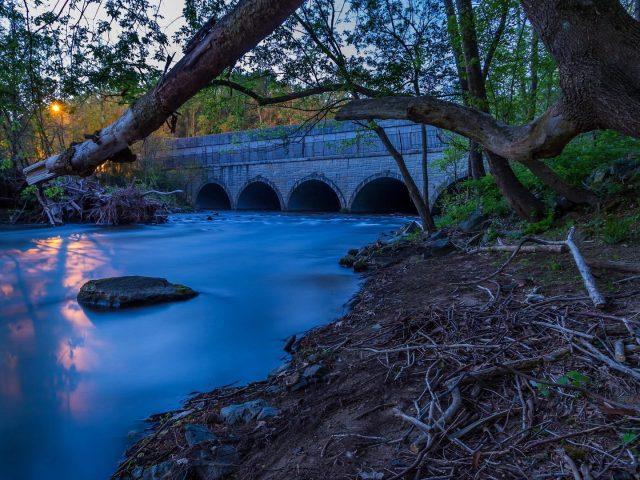 Закат над речным мостом вокруг зеленые деревья природа