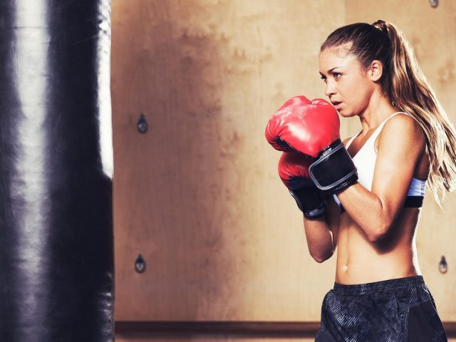 Девушка с конским хвостом в белом черном платье и красных боксерских перчатках бокс