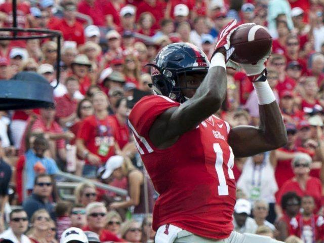 Меткалф высоко прыгает с мячом на заднем плане аудитории одетый в красное спортивное платье dk metcalf