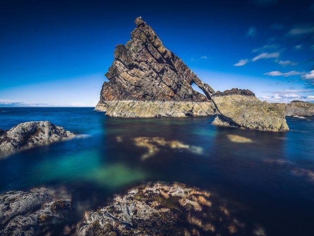 Скала посреди океана под голубым небом природа