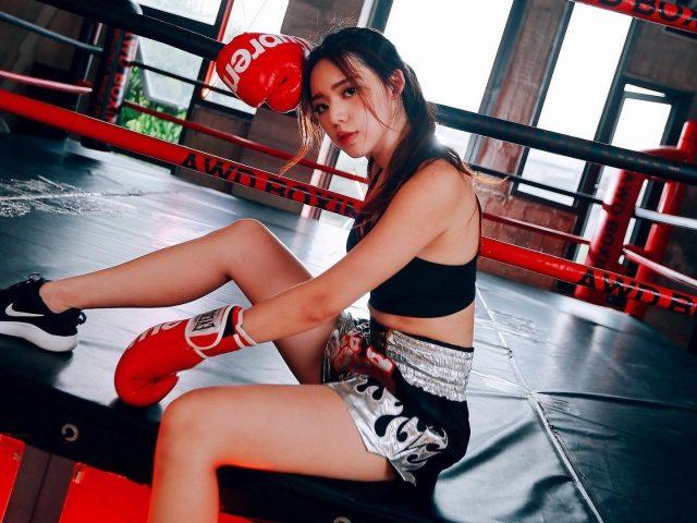 Девушка сидит на боксерском поле в черном платье и красных перчатках боксера