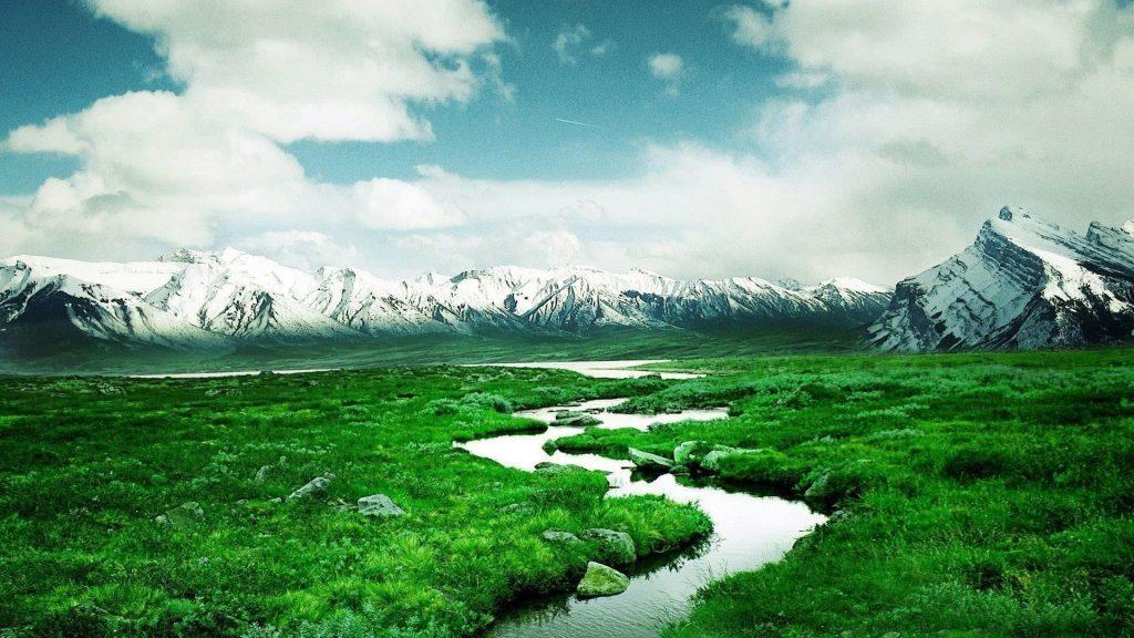 Река между лугами и пейзажем вид на заснеженные горы под облачным небом природа обои скачать