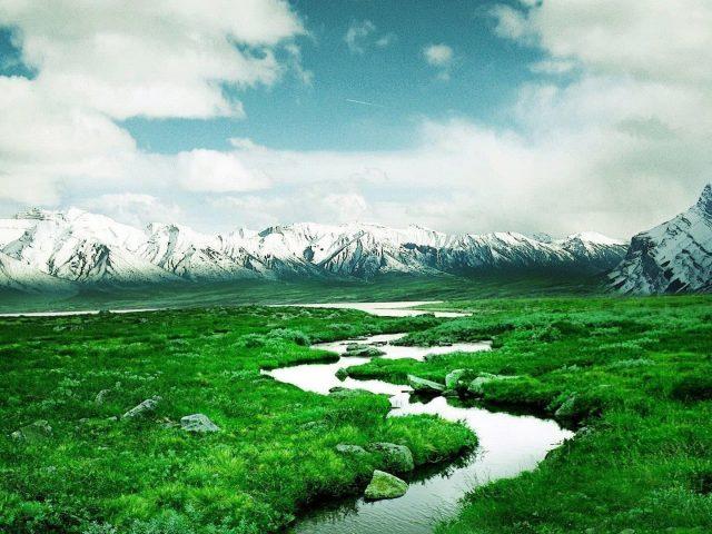 Река между лугами и пейзажем вид на заснеженные горы под облачным небом природа